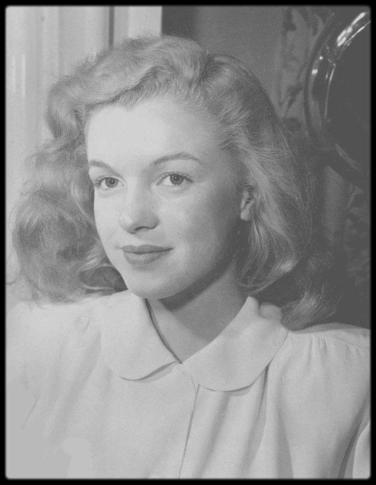 """1946 / METAMORPHOSE / Le 2 août 1945, la jeune Norma Jeane signe au sein de l'agence de mannequin « Blue Book Models Agency » dirigée par Emmeline SNIVELY. Dans son dossier d'entrée il est stipulé : « cheveux trop bouclés et indisciplinés, décoloration et permanente conseillées ». Au début de l'année 1946, sous les conseils de Miss SNIVELY, Norma Jeane se rend au salon de coiffure hollywoodien alors très en vogue, le """"Frank & Joseph Hair Stylists"""". Emmeline explique a Norma qu'éclaircir ses cheveux lui donnera plus de travail parce que les blondes attirent beaucoup mieux la lumière. C'est Sylvia BARNHART qui s'occupa de la transformation de la chevelure de Norma Jeane en un blond cendré. La couleur des cheveux de Marilyn changea les années suivantes passant du blond cendré au blond argenté ou encore blond miel. A chaque film correspond une teinte différente jusque 1952 où elle prit partie pour le blond platine. On peut tout de même remarquer un changement notoire lorsqu'elle signe un contrat de 6 mois à la Columbia le 9 mars 1948 pour laquelle elle tournera « Ladies of the chorus« . La star du studio est la grande Rita HAYWORTH. La coiffure de Marilyn est alors calquée sur celle de Rita. Cependant pas question de teindre la jeune recrue en rousse, la couleur reste blonde mais le traitement à l'eau oxygénée va les rendre platine. Beaucoup de stars des années 40 sont blondes comme Lana TURNER, Betty GRABLE, c'est la grande tendance du moment. Le traitement pour rester blonde platine comme son idole Jean HARLOW est très coûteux, Marilyn, à nouveau sans contrat, doit faire attention à son argent. Ses cheveux redeviennent plus foncés. Lorsqu'elle rencontre Johnny HYDE au début de l'année 1949, son style va encore évoluer. Sa blondeur s'accentue et ses cheveux raccourcissent mais ce résultat sera vraiment visible qu'à partir de 1950 avec les films « The Asphalt Jungle » et « All about Eve »."""