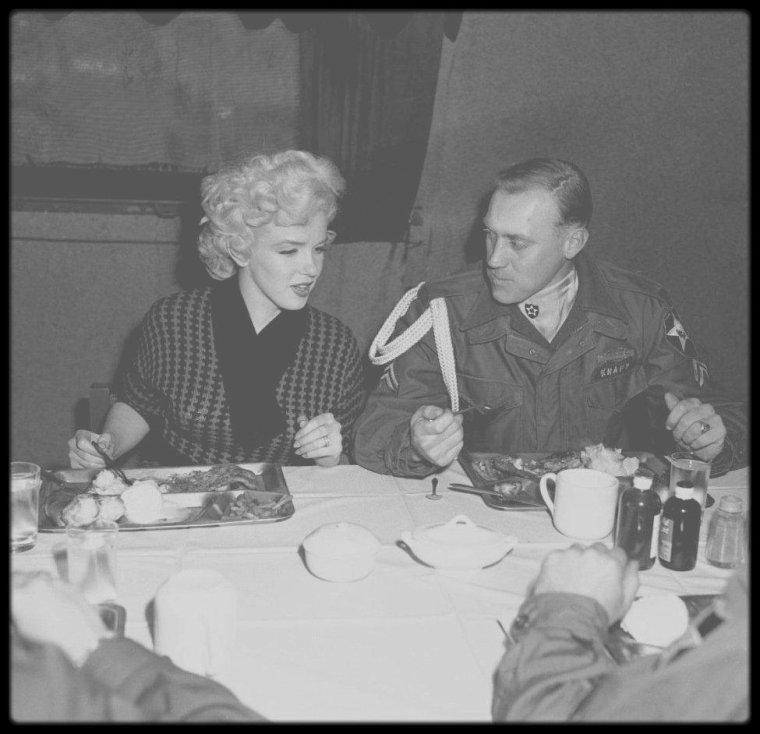 """18 Février 1954 / Marilyn est invitée au dîner de la deuxième infanterie lors de son séjour en Corée ; elle jouera l'espace d'un moment à la """"cantinière"""" avant d'être conviée à rejoindre la table des officiers."""