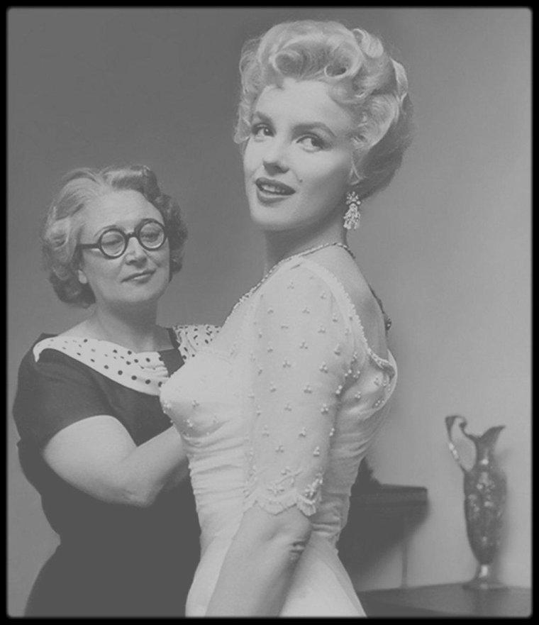 """1956 / Sur le tournage du film """"The Prince and the showgirl"""" / SYNOPSIS / Londres, 1911. Le prince régent des Carpates, le grand-duc Charles (Laurence OLIVIER), arrive en ville pour le couronnement de George V, accompagné de son jeune fils, le futur roi Nicholas (Jeremy SPENCER), et de sa belle-mère, la reine Dowager (Sybil THORNDIKE).  Après avoir vu la danseuse américaine de music-hall Elsie Marina (Marilyn) se produire en spectacle, le prince l'invite, dans l'opulente ambassade des Carpates, tablant sur une petite intrigue amoureuse. La pragmatique Elsie parvient à sauver sa vertu, bien qu'elle soit saoule et finisse par s'endormir. Pendant la soirée, une crise politique survient : Nicholas, qui a comploté pour accéder au pouvoir sans attendre sa majorité, 18 mois plus tard, est enfermé dans sa chambre par son père. Malgré ses origines modestes, Elsie reçoit l'approbation de l'austère reine DOWAGER, qui fait d'elle une dame d'honneur pour la cérémonie du couronnement. Pour Elsie c'est l'occasion idéale de réconcilier le père et le fils. Finalement elle persuade le jeune Nicholas d'attendre son heure. Le prince, qui est à présent réellement amoureux d'Elsie, projette de retourner dans son pays avec elle et de l'épouser."""