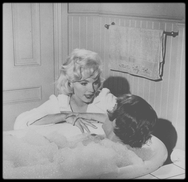 """1958 / Marilyn et Tony CURTIS dans une des scènes du film """"Some like it hot"""". / A PROPOS DU ROLE DE MARILYN / Le rôle de Sugar KANE a été fait sur mesure par Billy WILDER pour une Marilyn considérée comme trop tatillonne sur le choix de ses personnages, constamment soucieuse de l'image qu'elle renverrait d'elle au public. Malgré les difficultés rencontrées sur le tournage, elle y apparaît plus resplendissante que jamais. Sachant toujours où et comment placer son regard, ses petits rires, ses attitudes, elle irradie l'écran, faisant à la fois ressortir son côté d'icône sexuelle et de gentille fille vulnérable (on se souvient de son entrée en scène accueillie par un sifflement de train). Billy WILDER déclare à ce sujet : """"Ce que vous aviez réussi à lui arracher en vous accrochant, devenait étourdissant dès que vous le voyiez sur un écran. Etourdissant, tellement les radiations qui émanaient d'elle étaient fortes. Et c'était une excellente actrice pour les dialogues. Elle savait où ménager des pauses pour permettre au public de rire."""" Pour tout cela, la scène la plus marquante du film reste sans aucun doute sa fameuse interprétation de """"I wanna be loved by you"""", que le critique Roger EBERT considère comme """"un strip-tease dans lequel la nudité aurait été superflue."""" En alchimie totale avec la caméra qui la filme, elle se sert de son corps comme d'un langage sexuel alors qu'elle chante innocemment une chanson pleine de naïveté. Marilyn elle même, avec toutes ses contradictions, voici ce qui transparaît derrière le personnage de Sugar KANE."""