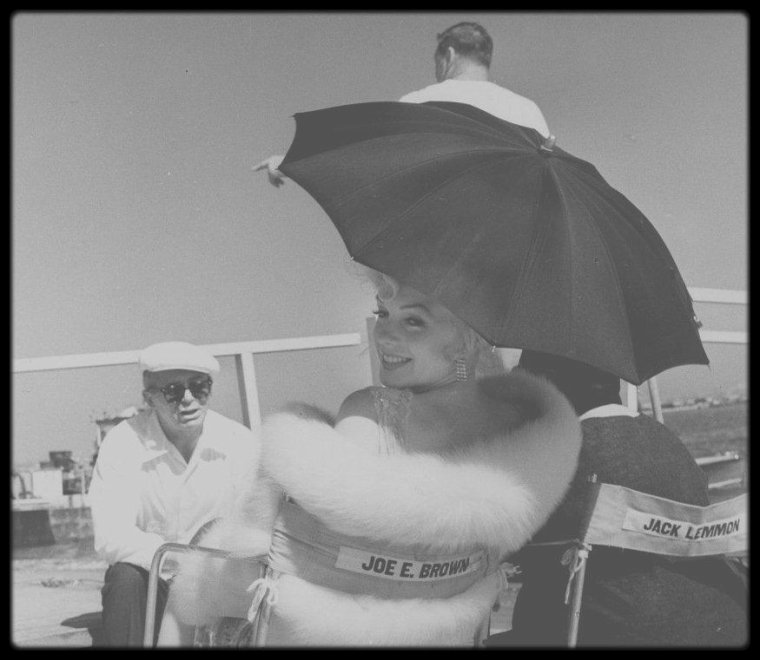 """1958 / Sur le tournage de """"Some like it hot"""", avec Paula STRASBERG, Tony CURTIS ou encore Billy WILDER / A PROPOS / Il fallait une actrice qui puisse à la fois provoquer l'excitation et toucher le c½ur du public, une synergie importante sur le papier qui s'est révélée cruciale à l'équilibre et au succès du film grâce à la présence de Marilyn MONROE. « Les deux rôles importants étaient ceux des deux hommes qui doivent s'habiller en femmes, c'est là-dessus qu'on comptait » se souvient WILDER. « Mais le bonus est arrivé ! Nous voulions n'importe quelle fille parce que ce n'était pas un rôle important, on pensait à Mitzi GAYNOR. Puis on a appris que Marilyn voulait le rôle : dès ce moment il nous fallait Marilyn. On a ouvert toutes les portes pour l'obtenir et on l'a eue. L'intrigue et la présence de Marilyn créaient une telle tension dramatique pour le spectateur que cela ne pouvait se décharger autrement que par une sorte d'explosion comique. On avait une belle bombe à tirer dans ce canon… » Marilyn apparaît comme un fantasme vivant : c'était la femme la plus désirée du monde, à l'époque. « Il y avait en elle une sorte de vulgarité élégante. » Sugar, son personnage, est une jeune femme innocente qui souffre de l'effet de sa beauté sur les hommes. WILDER capte cette faille et trouve là l'originalité supplémentaire d'un personnage plus complexe qu'il n'y paraît, à laquelle le réalisateur ajoute quand même un soupçon de cupidité (intéressée par l'argent, elle est prête à partager la vie de quelqu'un, du moment qu'il est milliardaire). « Elle avait saisi le personnage, qui en fin de compte était toujours le même, d'ailleurs. C'est comme ça qu'elle voulait que ce soit. » Ainsi, pleine de contradictions, entre l'image torride et la gentille fille sage, Sugar ressemble étrangement à Marilyn elle-même. WILDER joue avec l'arrogante beauté de la star et ne se prive pas de la montrer sous tous les angles en prétextant d'adopter le regard gourmand des deux héros (gros plan des fe"""