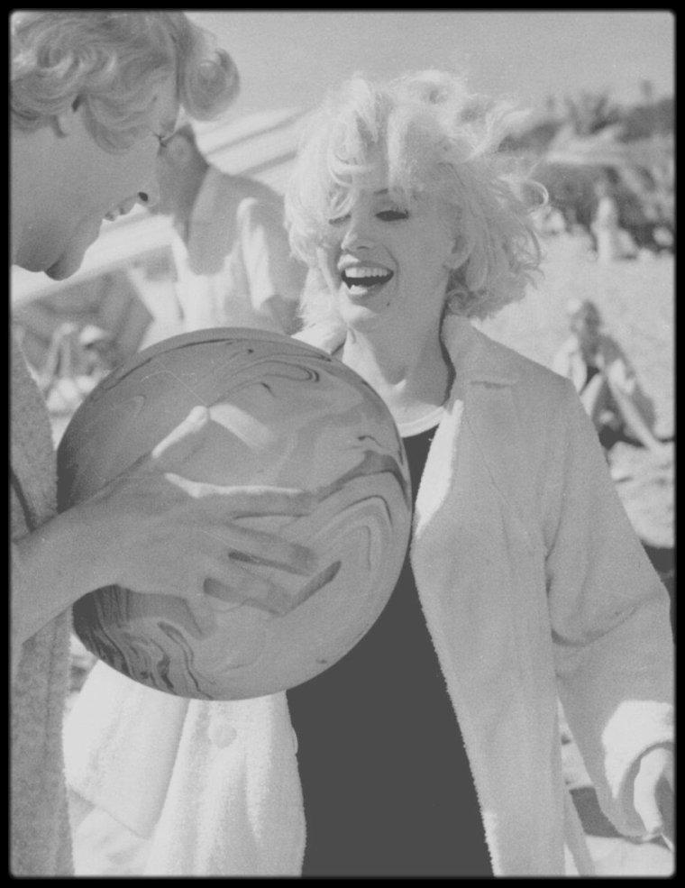 """1958 / MARILYN ET JACK LEMMON : """"DEUX COPINES DE TOURNAGE"""" /  Dès juin 1958, le casting se dessine et l'idée de Frank SINATRA dans le rôle de Joe est vite abandonnée. Tony CURTIS est déjà une star, comme Marilyn qui fait part via son agent (le même que WILDER et CURTIS) de son désir de jouer Sugar. Quant à Jack LEMMON, sous contrat à la Columbia, « Il était terriblement drôle, et il était tout nouveau. », dira WILDER. En revanche la rencontre au sommet des anciennes vedettes du film de gangsters n'aura pas lieu : Edward G. ROBINSON refuse le rôle de Little Bonaparte car il s'est déjà battu sur un plateau avec George RAFT (Spats). La fin des années 50 marque le passage généralisé à la couleur. Mais pour WILDER, le noir et blanc s'impose : il a situé son film dans les années 20 pour que le travestissement paraisse plus vraisemblable. « Si tous les costumes paraissent bizarres, alors ceux des travestis ne semblent pas plus singuliers que les autres. ». En fait, WILDER aime le noir et blanc, comme son directeur de la photographie Charles LANG, avec qui il a tourné """"La Scandaleuse de Berlin"""", """"Le Gouffre aux chimères"""" et """"Sabrina"""". Jusqu'au dernier moment, Marilyn, qui exige habituellement la couleur pour des raisons de photogénie, ignore que """"Certains l'aiment chaud"""" sera en noir et blanc. La vraisemblance du travestissement sert donc surtout de prétexte pour la convaincre de déroger à sa règle. De fait, le changement de sexe de LEMMON et CURTIS relève du défi. WILDER fait venir d'Europe un as du transformisme pour « coacher » ses acteurs. L'invité démissionne après un jour sur le plateau : CURTIS apprend vite, mais LEMMON est un cas désespéré. L'acteur fera de sa maladresse masculine sur hauts talons un atout comique évident. Ultime test pour les costumes et le maquillage : WILDER envoie CURTIS et LEMMON se repoudrer aux toilettes pour dames du studio. Les actrices n'y voient que du feu. Le tournage peut commencer. En août 1958, le tournage prend du retard lorsque Mari"""