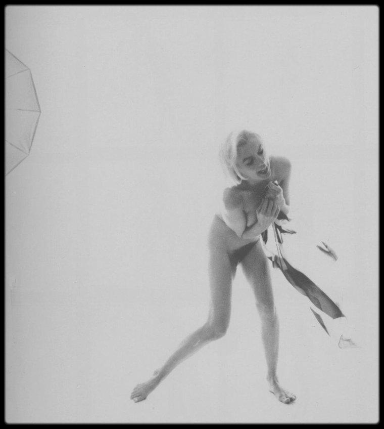 """1962 / DERNIERE SEANCE / Dans les coulisses d'une session photos qui dura 3 jours, 12 heures de travail, 2700 photos prisent par Bert STERN, Marilyn coiffée par Kenneth BATTELLE, photos commandées par le magazine """"Vogue"""". / SA RENCONTRE AVEC MARILYN MONROE / Pour l'éternité donc, Bert STERN (1929-2013) est celui qui a fait sourire Marilyn nue, chair tendre à peine distanciée par le voile de Salomé, offrant à l'objectif la cicatrice laissée par sa récente opération de la vésicule biliaire, la maturité de sa poitrine, sa taille fine retrouvée, son sourire presque trop grand comme les enfants punis, comme si la vie n'avait plus rien à cacher. """"The Last Sitting"""", c'est Marilyn ronde et rose derrière le foulard pop et scintillant qui, d'instinct, fait valoir son corps bien porté comme celui d'une danseuse. C'est Marilyn déguisée cruellement en Jackie KENNEDY, sa brune rivale en amour présidentiel. C'est la beauté apprêtée au platine extra-terrestre, qui s'abrite derrière un collier baroque. C'est la naïade qui souligne la cambrure de ses reins par une pose tonique. C'est l'aguicheuse qui cache ses seins par deux fleurs de soie et fait un clin d'½il entendu au regard voyeur. C'est aussi les clichés frontaux, presque naturistes, que la star a barrés d'une croix rouge. Un signe fort symbolique si près de la mort de son adorable sujet, et qui signifiait son veto définitif à toute image jugée non glamour. Le 21 juin 1962, Bert STERN a rendez-vous avec Marilyn à Los Angeles pour le """"Vogue"""" de septembre (un numéro posthume retentissant). Il revient de Rome et du tournage de """"Cléopâtre"""" avec Liz TAYLOR, grande rivale en renommée et surtout en cachets faramineux de Norma Jeane BAKER, comme en témoigneront les portraits respectifs, lunaire pour Liz, solaire pour Marilyn, de WARHOL. «Quand on évoque Marilyn MONROE, on repense à la photo célébrissime de Tom KELLEY en 1949, pour laquelle elle avait posé nue sur un fond en velours rouge, ou à sa robe blanche s'envolant autour d'elle d"""