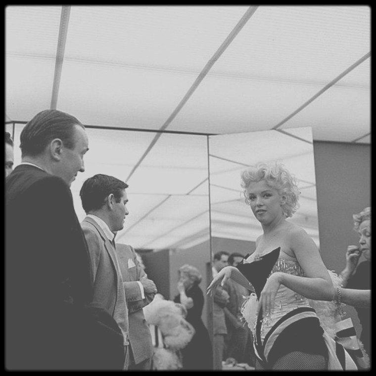 """30 Mars 1955 / L'après-midi du 30 mars 1955, Marilyn se rend à une séance d'habillage chez """"Brooks Costume"""", à New York, pour essayer le body à strass et le collant à résille très sexy brodé de paillettes et de plumes qu'elle portera le soir-même à la cérémonie de bienfaisance au """"Madison Square Garden"""", juchée sur un éléphant peint en rose. Elle aurait éclaté en sanglots tandis qu'on plante des épingles et qu'on la tiraille de toutes parts. Le photographe Milton GREENE resta à ses côtés pour donner son accord final. James STROOCK, propriétaire du magasin de costumes, supervise la séance, assisté de sa meilleure habilleuse, Mary SMITH. Dick SHEPERD qui était alors agent au département cinéma de MCA à New York, se souvient que la mission de MCA était de """"se démener pour la sortir de la prison dorée où la Fox l'enfermait. Ils s'imaginaient qu'ils pouvaient la contraindre à ne pas travailler"""". Il raconte que Marilyn était """"intransigeante sur l'idée qu'elle se faisait de son travail"""". H.D. QUIGG, était un journaliste """"d'United Press"""", a écrit au journal """"L.A. Style"""" pour un numéro spécial consacré à Marilyn en février 1988, pour décrire cette journée en détails : """"... On apprit que la presse aurait une chance d'être admise à l'essayage du costume de cornac de Miss MONROE. En tant qu'expert de la place pour tout ce qui touchait à TODD de près ou de loin, j'y allai. Miss MONROE devait arriver à 10h ou 10h30, mais bien sûr, elle ne s'est pas montrée... Le couloir d'accès était bondé de journalistes, principalement de baratineurs de la télé et de machinistes avec leur quincallerie. Vers midi, il devint évident qu'elle ne désirait pas affronter la foule, aussi la presse dut-elle plier bagage. Le propriétaire du magasin fonça sur moi et me dit """"Revenez donc vers 2 heures"""". J'ignore pourquoi il me choisit, moi, si ce n'est parce que j'avais l'air calme; en tout cas, je n'avais rien à voir avec cette clique. A 14 heures, j'arrivai et le propriétaire était là. Peu après, l'ascen"""
