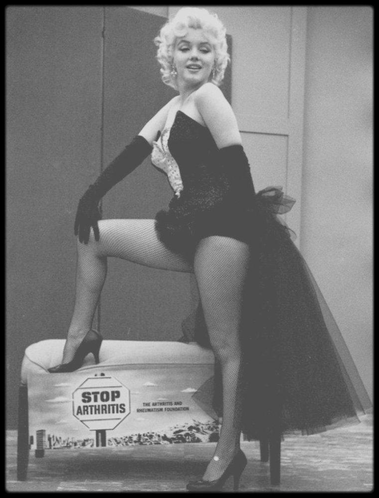 """30 Mars 1955 / (Part V) Le grand show, qui se tient au """"Madison Square Garden"""" à New York, était présenté par Milton BERLE, qui officiait en tant que """"Monsieur Loyal"""", le 'maître de cérémonie', et qui présente Marilyn en ces termes : """"Voici la seule femme au monde à côté de qui Jane RUSSELL ressemble à un homme!"""", provoquant l'hilarité dans la foule. Plus de 25 000 spectateurs étaient présents ; ils avaient payer 50 dollars leurs places ; dont Joe DiMAGGIO, l'ex-époux de Marilyn. Dans la salle, deux cents photographes s'arrachaient les meilleures places (Ed FEINGERSH, Milton GREENE, Marvin SCOTT, Walter CARONE, WEEGEE, Sam GOLDSTEIN, Erika STONE...). Lorsqu'enfin elle entra en scène, Milton BERLE dut leur demander de s'accroupir pour ne pas gêner les autres spectateurs. Marilyn fit une entrée triomphale, juchée sur le dos d'un éléphant indien peint en rose, nommé Karnaudi (ou Kinardy), appartenant au cirque """"Barnum & Bailey"""". Elle déclarera plus tard : """"C'était très important pour moi, je n'étais jamais allée au cirque quand j'étais enfant."""" Le magazine """"Variety"""" écrivit : """"Marilyn MONROE juchée sur un pachyderme peint en rose fut le clou de la soirée. Malheureusement, les photographes agglutinés autour de la star à demie nue l'empêchaient d'avancer. On put difficilement admirer les charmes de Miss MONROE, mais en définitive, la foule ne s'était déplacée pas pour rien."""" Les autres stars présentes furent toute au plus citées."""