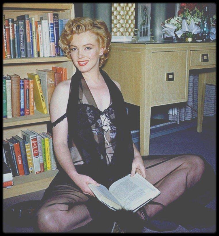 """1952 / Marilyn dans son studio du """"Beverly Carlton Hotel"""", sous l'objectif de Philippe HALSMAN et Harold LLOYD. / Le photographe Philippe HALSMAN s'étonna de l'aménagement : """"Ce qui m'a frappé dans ce minable petit salon, c'étaient les efforts évidents que faisait cette petite blonde réputée sotte pour son évolution personnelle. J'ai vu une photo d'Eleonora DUSE et une multitude de livres auxquels je ne m'attendais vraiment pas : DOSTOÏEVSKI, FREUD et """"L'histoire du socialisme"""" FABIEN."""" Pour cette séance photos, Philippe HALSMAN était accompagné de son assistant Harold LLOYD (l'acteur mais aussi photographe), qui prit notamment les photos en couleur."""