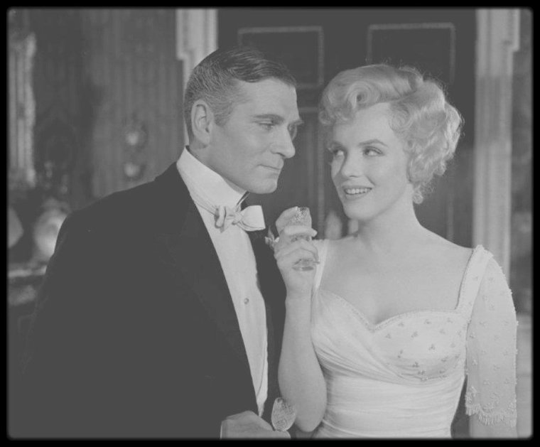 """1956 / Sur le tournage du film """"The Prince and the showgirl"""", sous l'objectif du photographe Milton GREENE. / PROPOS de Laurence OLIVIER sur Marilyn : - """"Ma haine pour elle est l'une des émotions les plus fortes que j'aie jamais ressenties."""" Le tournage n'aurait pu débuter plus mal : Marilyn, qui se débarrassait enfin du carcan des rôles sexy auxquels on l'avait cantonnée, et appliquait avec empressement l'introspection et la recherche de motivation prônées par """"la Méthode"""", reçut de Laurence OLIVIER l'instruction « d'être sexy ». Par représailles envers ce qu'elle prenait pour de la condescendance, Marilyn eut recours à sa tactique éprouvée : le retard et les absences. Selon le directeur de la photographie, Jack CARDIFF, les problèmes entre Laurence OLIVIER et Marilyn surgirent parce qu'ils avaient des approches différentes du jeu de l'acteur. Au milieu du tournage, la psychanalyste de Marilyn, le Dr Margaret HOHENBERG, accourut à Londres pour aider sa patiente. Les tensions atteignirent bientôt leur paroxysme. Laurence OLIVIER pensait que Marilyn était susceptible, et il ne pouvait supporter ce qu'il considérait comme de l'ingérence de la part de Paula STRASBERG ; Paula servait souvent d'intermédiaire entre Marilyn et lui, faisant circuler l'information entre les deux vedettes du film, qui ne se parlaient plus. Milton GREENE se méfiait d'Arthur MILLER, et Marilyn, à ce que l'on raconte, avait commencé le tournage en proie aux soupçons, après avoir lu dans le journal intime de son mari un passage qui avait détruit sa confiance en lui. En dépit des frictions et des rumeurs, le film ne dépassa pas le budget, et il ne fallut que deux jours pour refaire certaines scènes. Même après le tournage, les disputes continuèrent. A l'époque Marilyn s'était brouillée avec Milton GREENE, convaincue qu'il avait procédé, à son insu, à de nouvelles coupures dans le film. Elle écrivit une longue lettre à Jack WARNER pour lui en faire part, et elle fit de son mieux pour que GREENE ne """