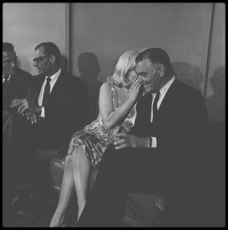 """24 Juillet 1960 / (Part III) Conférence de presse au sein d'un salon du """"Mapes Hotel"""", à Reno, Nevada, lieu de tournage du film """"The misfits"""", avec le réalisateur John HUSTON ou encore Arthur MILLER, les acteurs du film tels Montgomery CLIFT, Clark GABLE, Eli WALLACH ou Thelma RITTER, ainsi que les photographes de l'Agence """"Magnum"""", couvrant l'événement. On notera que Marilyn porte une perruque lors de la soirée, qui s'avèrera être aussi celle du film, ses cheveux étant tellement abîmés par les décolorations fréquentes."""