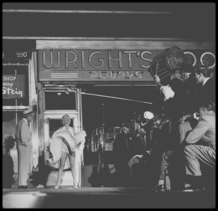 """15 Septembre 1954 / Sur le tournage de la scène la plus culte du cinéma Américain, voir mondiale, où Marilyn décroche, le titre d'actrice la plus connue dans le monde. / Entre la 51 et 52st Street, au croisement de Lexington Avenue, New York City, il s'agit d'une scène mythique, l'une des plus célèbres de l'histoire du cinéma, qui reste sans doute la """"scène la plus vue au monde"""", celle où la robe blanche de Marilyn se soulève entraînée par l'air d'une grille de métro. La presse en parla comme de """"l'exhibition la plus intéressante depuis """"Lady Godiva"""". Le soir du 14 septembre 1954, la police dressa des barrières de bois devant le cinéma """"Trans-Lux Theater"""", au carrefour de Lexington Avenue et de la 52nd Street. Le département publicité des studios n'avait pas manqué l'occasion de prévenir la presse en communiquant le lieu exact du tournage et en garantissant que la circulation serait bloquée. Vers une heure du matin (donc le 15 septembre 1954), alors que le tournage devait débuter, plusieurs centaines de photographes et journalistes se bousculaient pour prendre place, au milieu d'une foule de milliers de spectateurs (d'après Billy WILDER, il y avait près de 5 000 personnes ; mais un journal avança le nombre d'environ 1 000 personnes), qui appréciait chaque moment en poussant des hourras et en criant avec frénésie """"Plus haut ! Plus haut !"""", chaque fois que la jupe de Marilyn s'envolait. Le tournage dura cinq heures et il y eut quinze prises. Le vent était géré par une machine installée en-dessous de la grille d'aération du métro, sur laquelle Marilyn prenait place. Le responsable des effets spéciaux, Paul WURTZEL, avait fait placer un gigantesque ventilateur, afin que le courant d'air soit assez puissant pour soulever la robe de Marilyn et ainsi dévoiler ses jambes et sa culotte blanche. C'est pour cette raison que Marilyn, prévoyante, portait deux culottes blanches superposées, afin d'éviter tout effet de transparence, bien que certains ont suggéré le contraire (comm"""