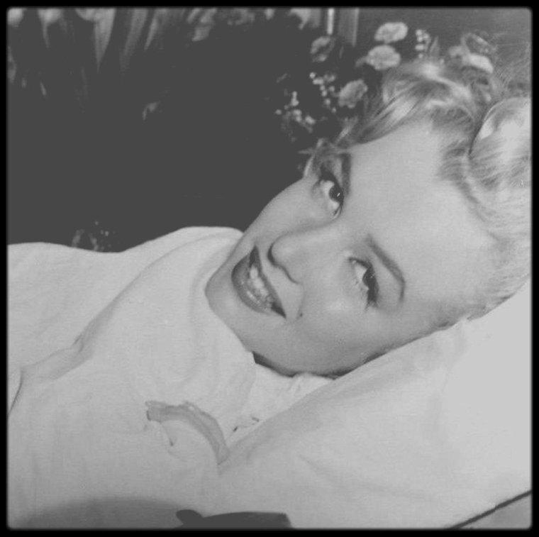 """28 Avril 1952 / (Part II) Marilyn se fait opérer de l'appendicite au """"Cedars Lebanon Hospital"""". Pendant sa convalescence, elle reçoit un reporter photographe dans sa chambre d'hôpital, où on la découvre en train de lire une carte de Joe DiMAGGIO, qu'elle fréquente depuis quelques mois. A côté de son lit, se trouve un bouquet de roses envoyées par Joe. Marilyn avait eu des douleurs à l'appendice en mars de la même année, mais étant alors en plein tournage de """"Monkey business"""", l'opération fut reportée en mai.  > Photographies prises le 6 mai, jour de sa sortie Marilyn a été opérée la semaine précédente."""