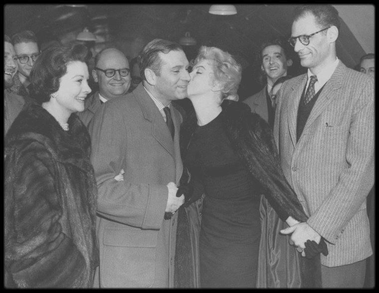 22 Novembre 1956 / (Part III) Laurence OLIVIER et Vivien LEIGH accompagnèrent Marilyn et Arthur MILLER à l'aéroport. Ils firent tous bonne figure, alors que leur vie à chacun avait été bouleversée depuis qu'ils s'étaient retrouvés là en juillet : Vivien LEIGH avait perdu son bébé et par là même, toute chance de sauver son mariage. Laurence OLIVIER avait raté l'occasion d'une renaissance personnelle qu'il espérait réaliser avant la cinquantaine. Arthur MILLER avait compris que la vie avec Marilyn allait être différente de tout ce qu'il avait imaginé. Et Marilyn, toujours bouleversée par ce qu'elle avait lu dans le cahier d'Arthur, avait toutes les raisons de croire que tant son mariage que son premier film indépendant étaient voués à l'échec. Pendant presque deux ans, elle ne tournera plus de films. Après une escale à Shannon, en Irlande, ils arrivèrent aux Etats-Unis.