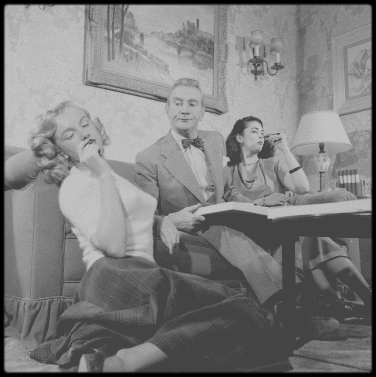 """1948 / (Part II) Marilyn se prête au jeu des photos, avec les acteurs Clifton WEBB et Laurette LUEZ, tournant alors une scène du film """"Sitting pretty""""."""