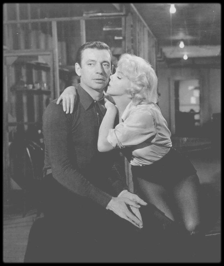 """1960 / Lors de cette Trente-deuxième Nuit des Oscars, Shelley WINTERS fut désignée comme meilleure interprète de second rôle féminin et, devant un parterre d'étoiles, Yves MONTAND chanta et dansa. Un garçon dansait en hommage à Fred ASTAIRE qui l'avait appelé sur scène. Un tonnerre d'applaudissements salua sa prestation, puis, comme le metteur en scène Vincente MINNELLI l'invitait à rejoindre sa place, MONTAND répondit : « Mais non, c'est maintenant l'Oscar de la meilleure interprète féminine, et Marilyn a dit à Simone qu'elle allait l'avoir ! » Rock HUDSON décacheta  l'enveloppe. Marilyn ne s'était pas trompée. Simone était attendue pour un tournage en Europe et, quelques jours plus tard, elle prit l'avion pour Rome, son Oscar sous le bras — et Marilyn resta avec le cher Yves. Peu après le retour des MILLER à Hollywood, Arthur s'envola pour l'Irlande afin d'y rencontrer John HUSTON et de lancer la production des """"Désaxés"""". MONTAND se demanda si sa connaissance approximative de l'anglais n'était pas en train de lui jouer des tours lorsque MILLER lui dit au revoir en ajoutant à voix basse : « Advienne que pourra. » Doris VIDOR, une amie de MONTAND et des MILLER, se souvient que MONTAND était « dans tous ses états » lorsqu'il l'appela au téléphone. « Il s'en va et me laisse avec Marilyn, dont l'appartement jouxte le mien ! s'écria-t-il. Comme s'il ne savait pas qu'elle est prête à se jeter dans mes bras ! » Doris se rappelle de sa réponse à MONTAND : « Yves, tout cela devient très compliqué. A votre place, je me méfierais. Qui vous dit qu'Arthur n'a pas fait exprès de s'en aller ? Il est peut-être las du fardeau qu'on lui fait porter, et trop heureux de s'en décharger aux pieds d'un autre... »"""