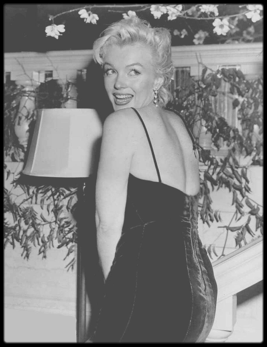 """9 Février 1956 / Conférence de presse au Terrace room du """"Plaza Hotel"""" de Londres, pour annoncer la production (Laurence OLIVIER, Terrence RATTIGAN et Milton GREENE) aux journalistes, du film """"The Prince and the showgirl"""". Les deux acteurs se congratulèrent mutuellement devant plus de 150 journalistes et photographes. Il s'agissait d'un événement majeur qui allait réunir un grand tragédien anglais et le plus grand sex-symbol de l'Amérique. Bien qu'elle ait nié toute préméditation, Marilyn orchestra l'événement à la perfection, volant la vedette au « plus grand acteur vivant au monde », lorsqu'elle se pencha en avant et que l'une des bretelles de sa robe (créée par John MOORE ) cassa net (un truc que les agents de publicité de la Fox lui avait semble-t-il appris à ses débuts). Les photographes devinrent fous. On lui procura en hâte une épingle à nourrice, mais la bretelle céda encore deux fois, devant des journalistes et photographes ravis  de l'incident."""