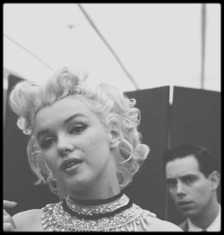 """30 Mars 1955 / Marilyn se rend à une séance d'habillage chez """"Brooks Costume"""", à New York, pour essayer le body à strass et le collant à résille très sexy brodé de paillettes et de plumes qu'elle portera le soir-même à la cérémonie de bienfaisance au """"Madison Square Garden"""". Elle aurait éclaté en sanglots tandis qu'on plante des épingles et qu'on la tiraille de toutes parts. Le photographe Milton GREENE resta à ses côtés pour donner son accord final. James STROOCK  (l'homme aux cheveux blancs), propriétaire du magasin de costumes, supervise la séance, assisté de sa meilleure habilleuse, Mary SMITH. Dick SHEPERD (l'homme mince aux cheveux bruns) et qui était alors agent au département cinéma de MCA à New York, se souvient que la mission de MCA était de """"se démener pour la sortir de la prison dorée où la Fox l'enfermait. Ils s'imaginaient qu'ils pouvaient la contraindre à ne pas travailler"""". Il raconte que Marilyn était """"intransigeante sur l'idée qu'elle se faisait de son travail"""". H.D. QUIGG, (l'homme aux lunettes et cheveux bruns frisés) était un journaliste d'""""United Press"""", a écrit au journal """"L.A. Style"""" pour un numéro spécial consacré à Marilyn en février 1988, pour décrire cette journée en détails : """"... On apprit que la presse aurait une chance d'être admise à l'essayage du costume de cornac de Miss MONROE. En tant qu'expert de la place pour tout ce qui touchait à Todd de près ou de loin, j'y allai. Miss MONROE devait arriver à 10h ou 10h30, mais bien sûr, elle ne s'est pas montrée... Le couloir d'accès était bondé de journalistes, principalement de baratineurs de la télé et de machinistes avec leur quincaillerie. Vers midi, il devint évident qu'elle ne désirait pas affronter la foule, aussi la presse dut-elle plier bagage. Le propriétaire du magasin fonça sur moi et me dit """"Revenez donc vers 2 heures"""". J'ignore pourquoi il me choisit, moi, si ce n'est parce que j'avais l'air calme ; en tout cas, je n'avais rien à voir avec cette clique. A 14 heures, j'arrivai"""