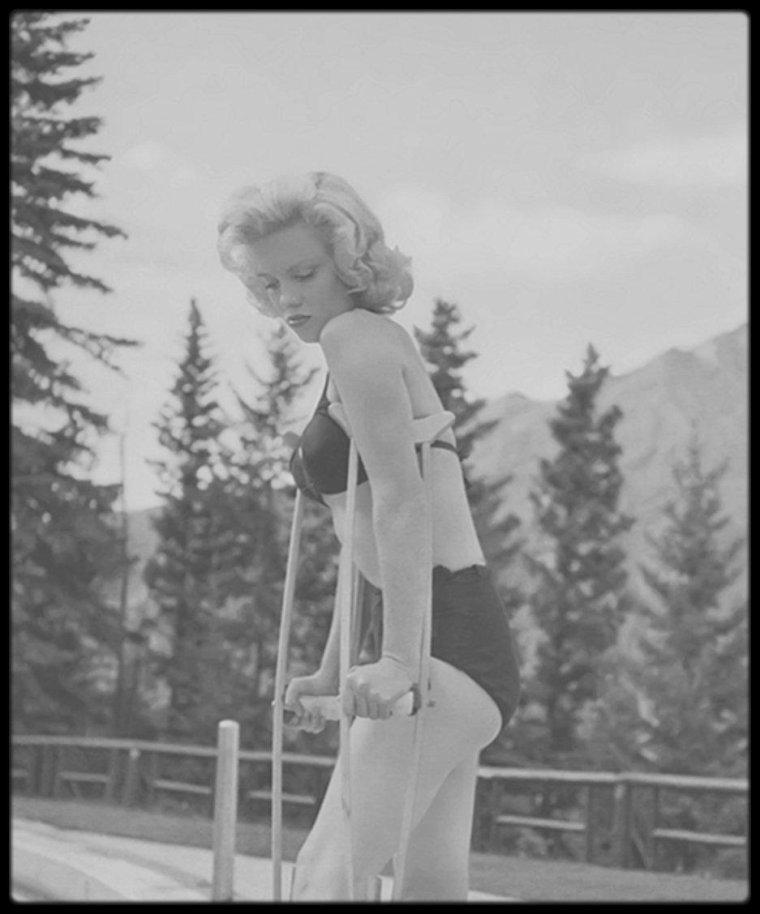 """1953 / Diverses photos sur le tournage du film """"River of no return"""". / Rarement une ballade aura si parfaitement illustré l'étoffe du film dont elle agrémente la vision. Il y a peu d'action dans ce western nonchalant, et encore moins sous la forme de fusillades. Un puma, un duo de prospecteurs se dresseront sur le parcours du trio, puis enfin les Indiens, juste avant le face à face final à Council City, lui-même tronqué : une empoignade de plus, un coup de feu hors champs et ce sera terminé. C'est à peu près tout. Le reste du temps, comme pour """"The Big Sky"""" de HAWKS, comme pour """"Wagon Master"""" de FORD ou pour le trop méconnu """"Across the wide Missouri"""" de WELLMAN, le récit se perdra en méandres et digressions dédramatisées, contemplatives et sensuelles, faisant avec un même bonheur un sort aux corps qui se livrent dans l'effort et aux âmes que la rivière, éternelle source purificatrice du western (""""Bend of the river"""", """"The naked spur""""), se chargera de laver de leurs préjugés. Le dialogue lui-même se pare parfois d'une poésie solaire des plus inattendues dans le genre : - I had to get money to get out. When I met Harry he wanted the same thing. Then he won the claim. It was our big chance ; a chance for both of us to get away. - Where ? - Out of the lives we were both living. Some place where people live like human beings. - That's in Heaven... - We weren't thinking of going quite that far with it.  Au terme de cet itinéraire, épuisant mais rédempteur, Matt et Kay auront appris à se défaire de cette défiance d'autrui qui les coupe du monde, et à se défaire de cette pudeur qui les empêche de s'avouer leur amour mutuel.  La merveilleuse alchimie du couple MITCHUM - MONROE est pour beaucoup dans le ton heureux et serein de ce beau récit d'apprentissage ; la quiétude, la force tranquille et naturelle émanant du grand Bob, ici dans un emploi sur mesure, offrant un contrepoint parfait à la fragilité refoulée de Marilyn. Il est de notoriété publique que l'actrice s'entendit t"""