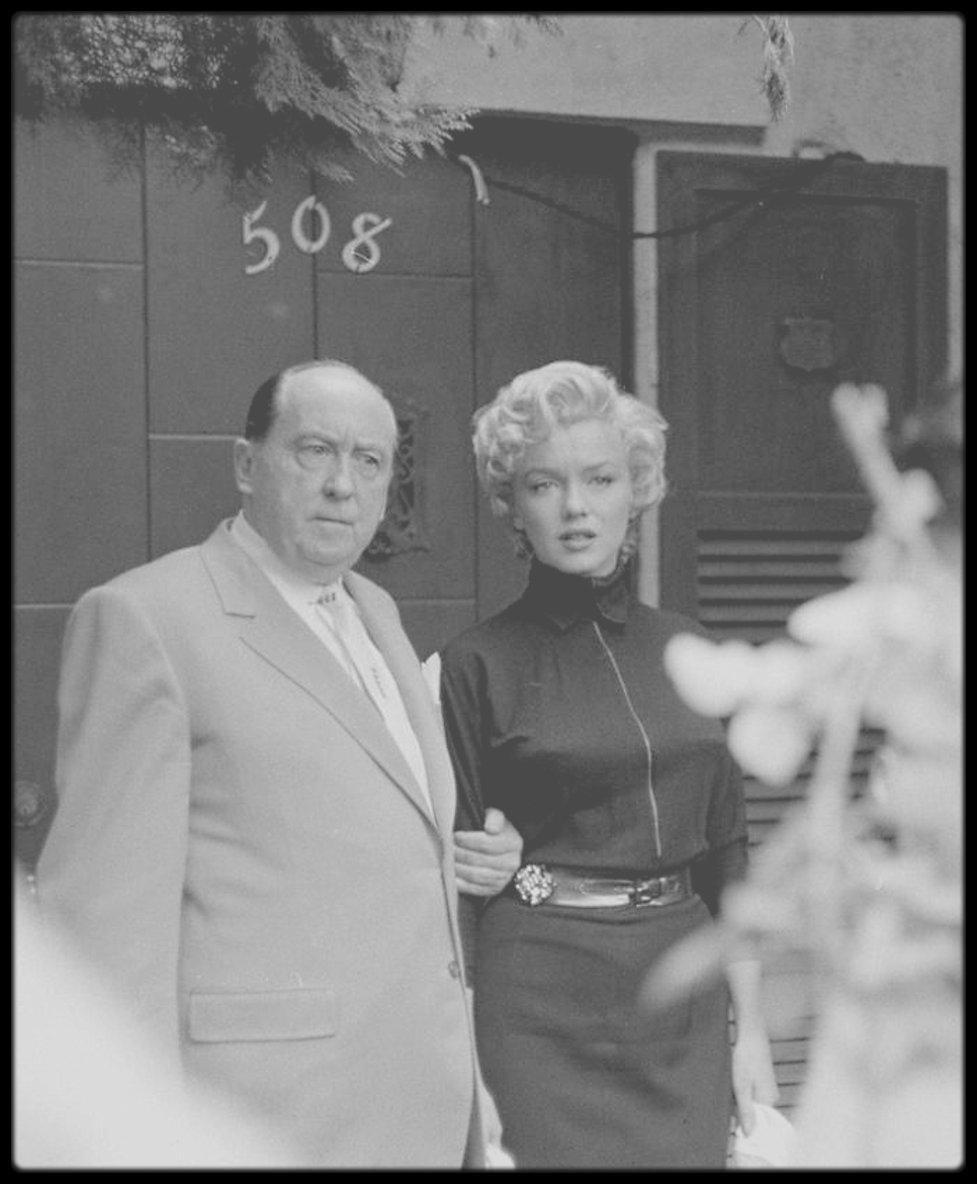 6 Octobre 1954 / (Part III) Annonce du divorce de Marilyn et de DiMAGGIO à la presse, en compagnie de son avocat Jerry GIESLER. / 508 North Palm Drive ; En 1954 elle habite au n° 508 avec DiMAGGIO. Ils emménagèrent dans cette maison quand Marilyn revint sur Los Angeles (après avoir habité à San Francisco avec le sportif) pour tourner « There's No Business Like Show Business » et « The Seven Year Itch ». Ils avaient loué cette  maison pour six mois. La maison de style Tudor comprenait huit pièces dont une réservée pour Joe DiMAGGIO Jr, avec une piscine et deux Cadillac noires. Elle donnait directement sur la rue. Un sentier en briques bordé de chrysanthèmes et de roses rouges s'incurvait jusqu'à la porte d'entrée. Ils payaient un loyer de 700 $ par mois (somme très élevée pour l'époque). Le 4 octobre 1954, c'est devant cette maison qu'ils annoncèrent leur intention de divorcer. Pendant les deux jours qui suivirent, la maison fut assiégée par la presse, les photographes et les fans.
