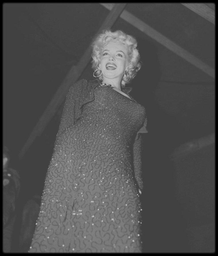 """Février 1954 / LES RARES de Marilyn lors de son séjour en Corée. / Robe de paillettes et escarpins à bout ouverts, Marilyn apparaissait toujours prête à monter sur scène. Même lorsqu'il s'agissait de rendre visite aux soldats américains en Corée alors qu'elle était en pleine lune de miel au Japon avec son mari Joe DiMAGGIO. Février 1954, le moral des troupes restées sur place après la fin de la guerre est au plus bas durant ce rude hiver. Débarque alors Marilyn MONROE, 28 ans, pimpante, qui pendant 4 jours va donner 10 spectacles devant 100 000 soldats et marins épuisés au bout de 3 ans de conflit.  L'héroïne de """"Certains l'aiment chaud"""" plaisante avec eux, endosse les vestes des officiers, signe des autographes et surtout prend le micro, moulée dans son fourreau."""