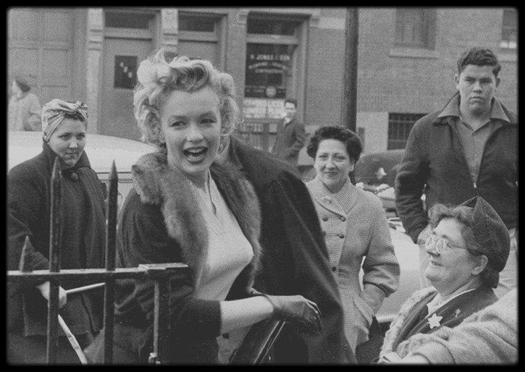 """4 Décembre 1956 / (Part III) Lors de la sortie américaine du film """"Baby Doll"""", Marilyn se rend à """"l'Actors Studio"""" de New York pour promouvoir le film. """"Baby Doll"""" est une adaptation cinématographique de la pièce de théâtre portant le même nom. La version cinéma a été réalisé par Elia KAZAN, le co-fondateur de """"l'Actors Studio"""", et met scène notamment l'acteur Eli WALLACH (avec qui Marilyn jouera dans le film """"The misfits""""), qui fréquenta les cours de théâtre. Marilyn aurait aimé jouer dans le film, mais le rôle féminin de """"Baby Doll Meighan"""" était celui d'une jeune fille mineure, jouée par Carroll BAKER qui était aussi une """"élève"""" de """"l'Actors Studio"""". Marilyn fait donc ici office d'ouvreuse (""""usherette"""") devant le théâtre; arrivant et repartant en taxi, elle pose avec l'affiche publicitaire du film. La chroniqueuse Louella PARSONS était là aussi."""