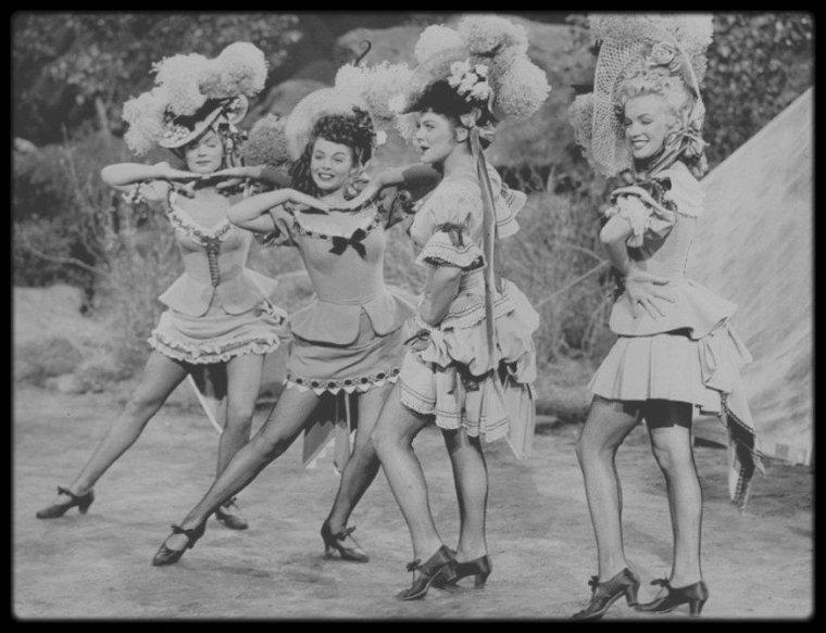"""1949 / Marilyn fait partie de la troupe des girls, dans le film """"A ticket to Tomahawk"""" de Richard SALE réunissant Anne BAXTER (avec qui elle jouera dans le film """"All about Eve"""" et Dan DAILEY qu'elle retrouvera dans le film """"There's no business like show business"""") ; le film sort aux Etats-Unis le 19 Mai 1950. / Ce film est un pastiche de western avec une histoire compliquée des tentatives d'un propriétaire de diligence pour empêcher la voie ferrée d'atteindre Tomahawk, dans le Colorado. Dans le train voyage une troupe de danseuses parmi lesquelles Carla (Marilyn MONROE). Elle eut à faire un numéro avec Dan DAILEY et trois autres danseuses. Retour à la Fox, mais pour un film savoureux, où Marilyn n'a pas plus à faire que dans ses quatre films précédents. Une brève mais sublime apparition. / Chanson interprétée par Marilyn : """"Oh, What a Forward Young Man You Are""""."""