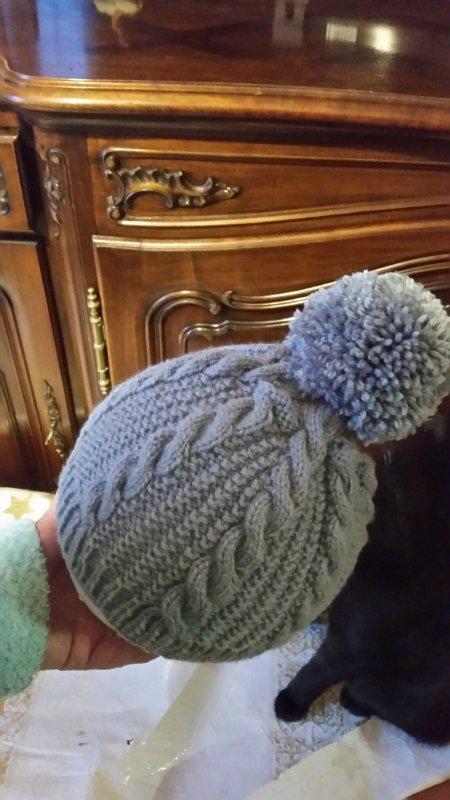 un bonnet gris à torsades avec un gros pompon assorti aux mitaines offertes pour Noël à ma petite cousine Nat...