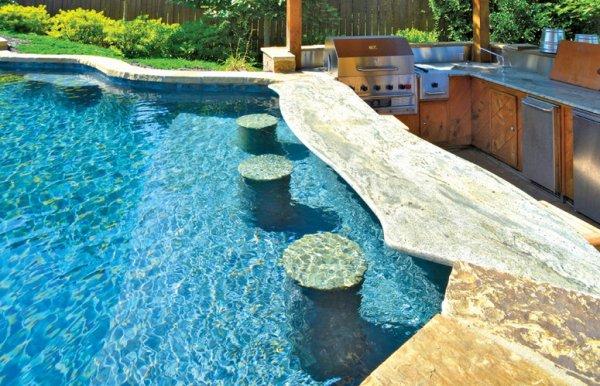 conception et realisation de piscine moderne en fausse roche, piscine a debordement ,avec mur d'eau,avec plage, lame d'eau, gua3da, mini bar,jacuzzy, tobogan et amenagement d'espace vert