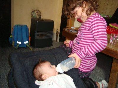 clara qui donne a boire a sa petite soeur :-)