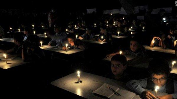 طلاب مدرسة فلسطينية يضيئون الشموع احتجاجا على تخفيضات الوقود الحادة